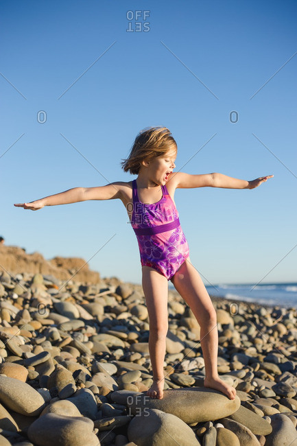 Young girl in swimsuit pretending to surf on a large rock on beach