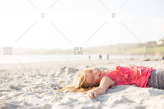 Happy young girl lying down on sandy beach
