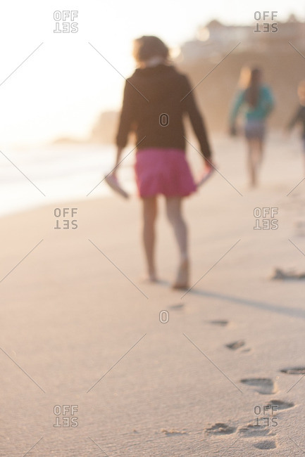 Young girl walking along the beach barefoot at sunset