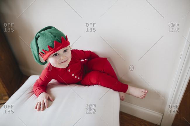Little boy in elf pajamas on an ottoman