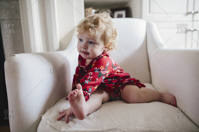 Toddler girl in red floral pajamas sitting in a chair