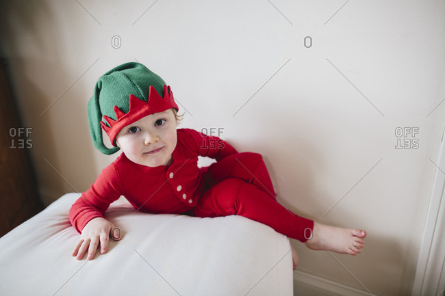 Boy in elf pajamas sitting on a stool