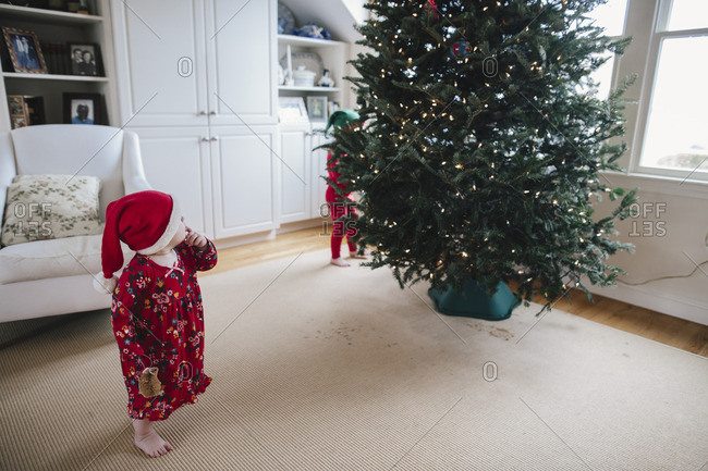 Children in red pajamas looking at a Christmas tree