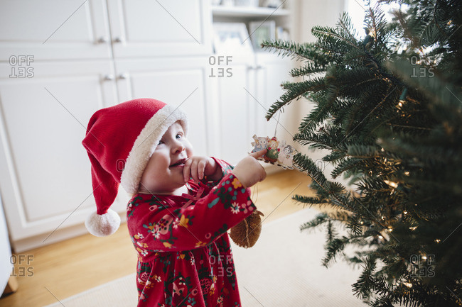 Toddler girl looking at ornaments on a Christmas tree