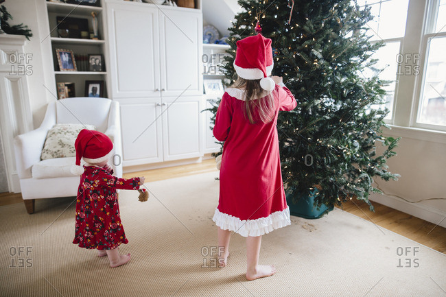 Two sisters in red pajamas decorating a Christmas tree