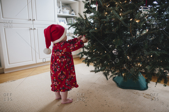 Toddler girl helping decorate a Christmas tree