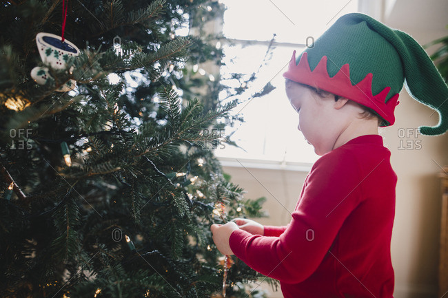Little boy in an elf hat helping decorate a Christmas tree