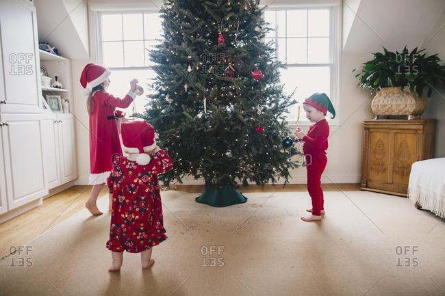 Three siblings decorating a Christmas tree