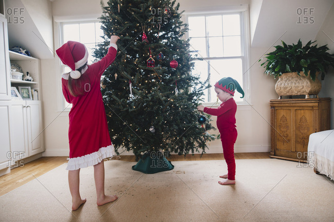 Brother and sister in red pajamas decorating a Christmas tree