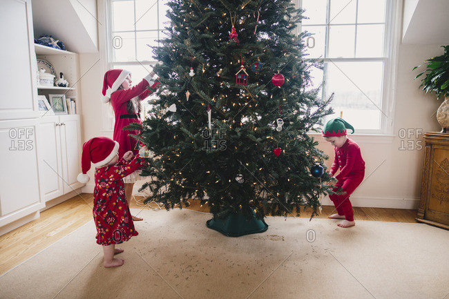 Three siblings putting ornaments on a Christmas tree