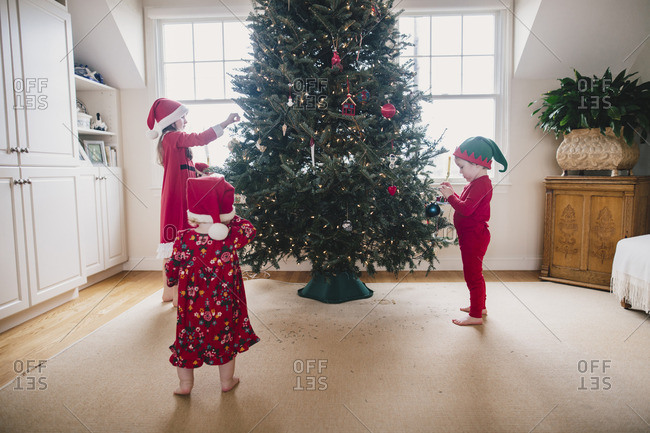 Sisters and brother decorating a tree for Christmas