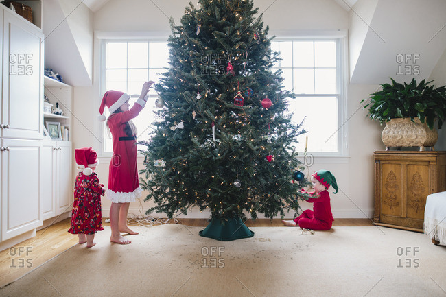Three siblings in red pajamas decorating a Christmas tree