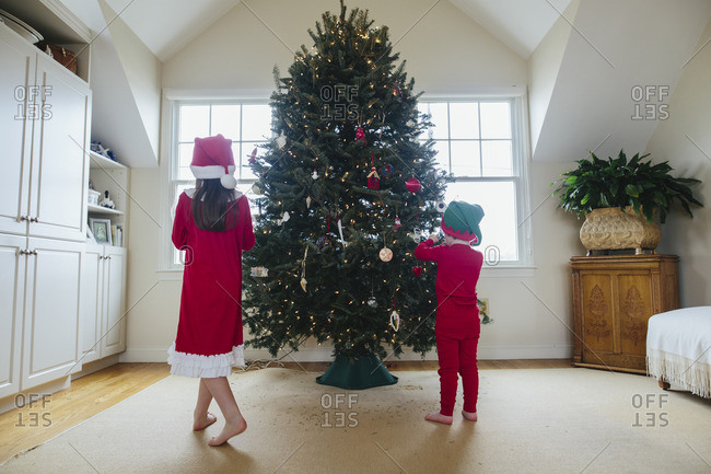 Boy and girl decorating a family Christmas tree together