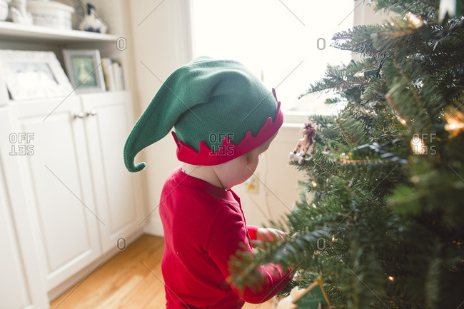 Little boy in elf pajamas decorating a Christmas tree