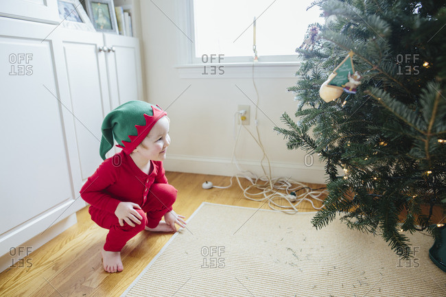 Little boy in elf pajamas looking at a decorated Christmas tree