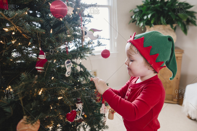 Boy in elf pajamas putting ornaments on a Christmas tree