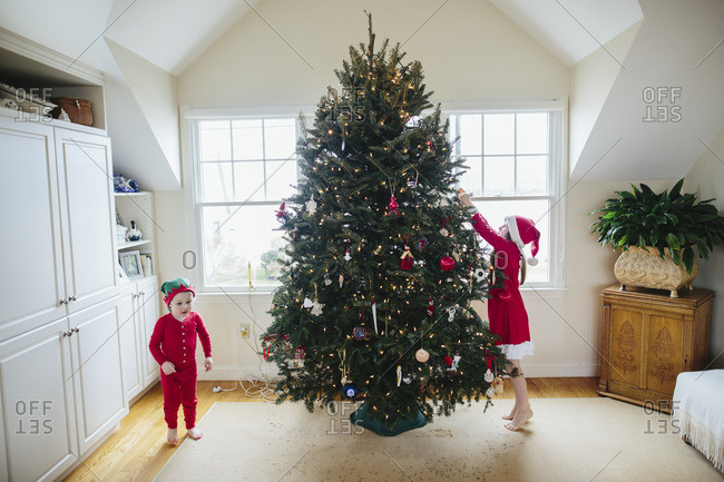 Boy and girl in pajamas decorating a Christmas tree