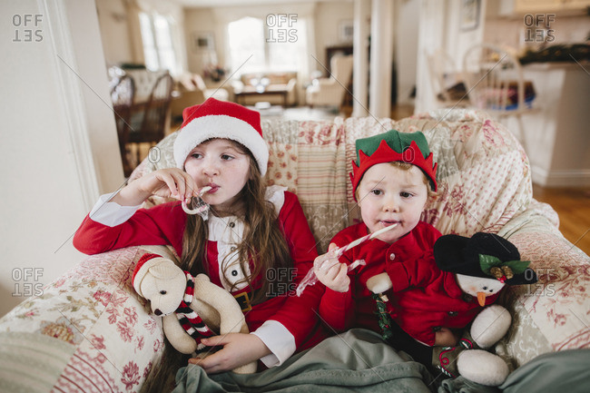 Brother and sister sitting in a chair eating Christmas candy