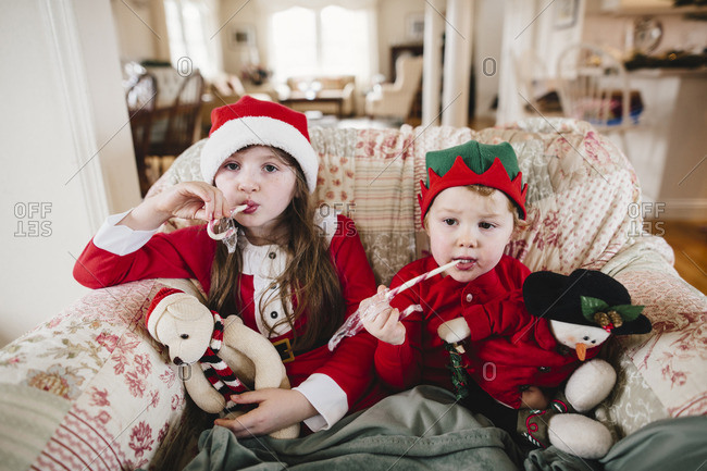 Two siblings in a chair with stuffed animals and Christmas candy