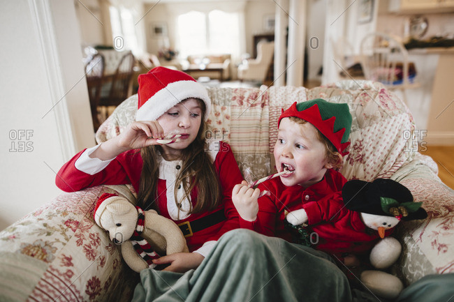 Sister and brother in a chair eating candy canes and holding stuffed toys