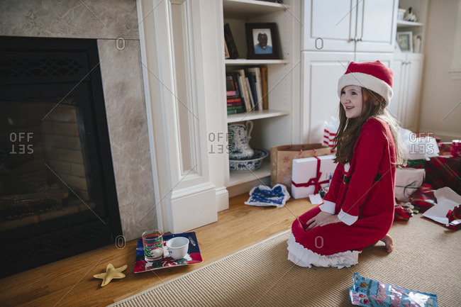 Girl in Santa pajamas looking at a plate of milk and cookies