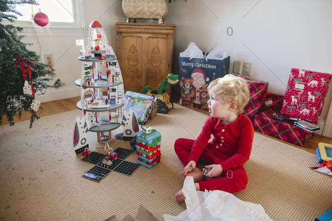 Little boy sitting on a rug looking at his Christmas gifts