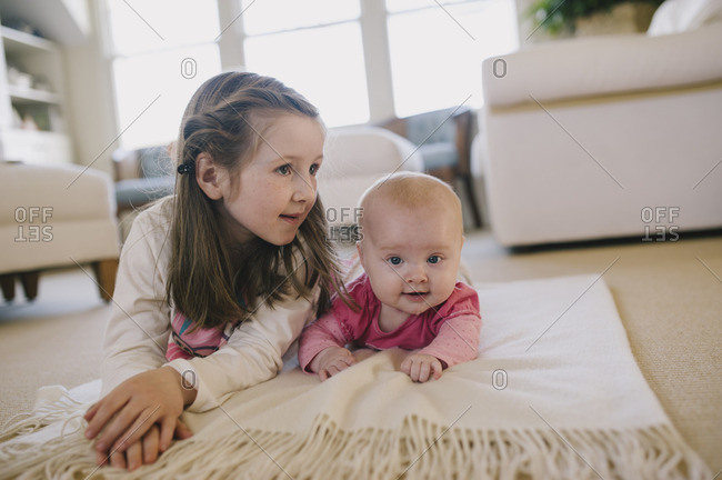 Girl lying on a blanket on her stomach with her baby sister