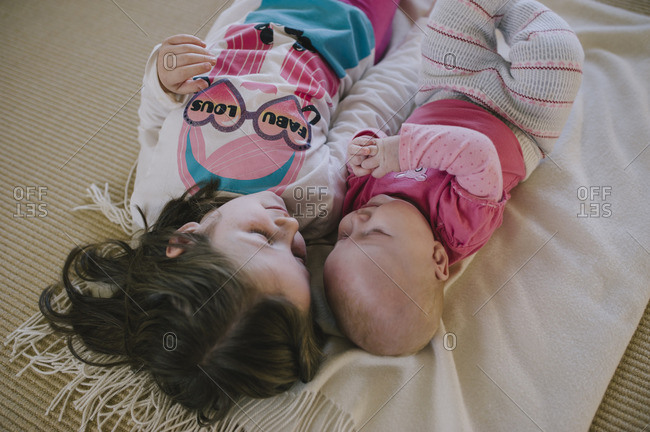 Little girl lying side by side with her baby sister on a blanket