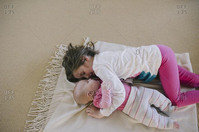 Little girl lying on a blanket cuddling her baby sister
