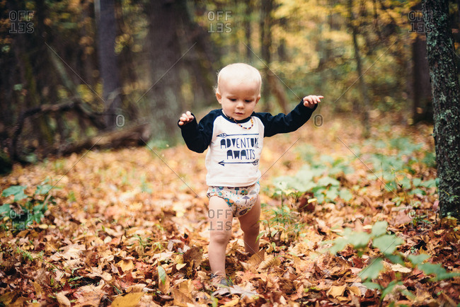 Baby boy walking in fallen leaves