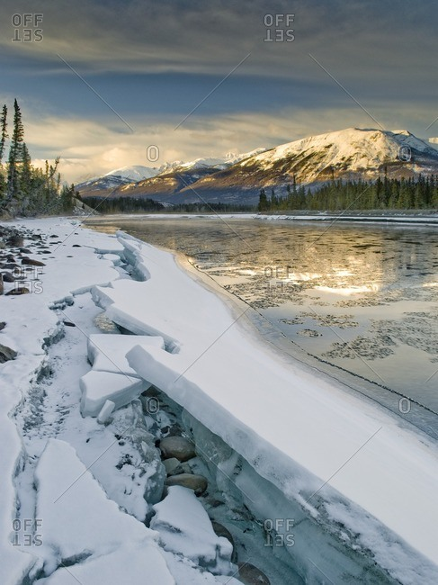 Ice puzzle forms on the Athabasca River during spring melt in the Rocky Mountains near Jasper, Alberta, Canada.