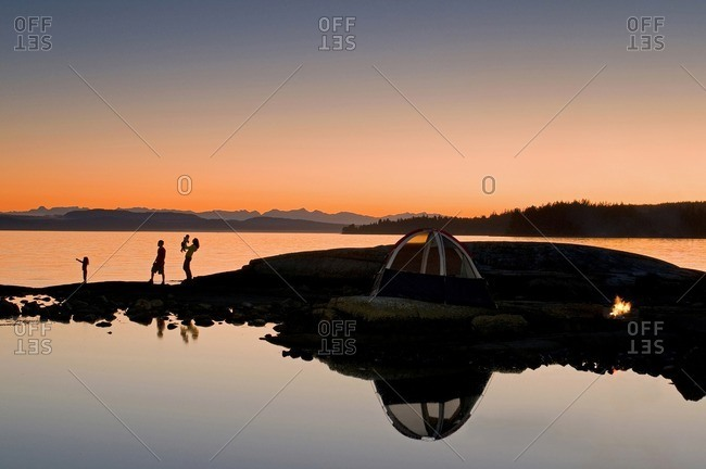 A family enjoys a captivating sunset while camping near Powell River, on the Sunshine coast of the Vancouver coast and mountain region of British Columbia, Canada.