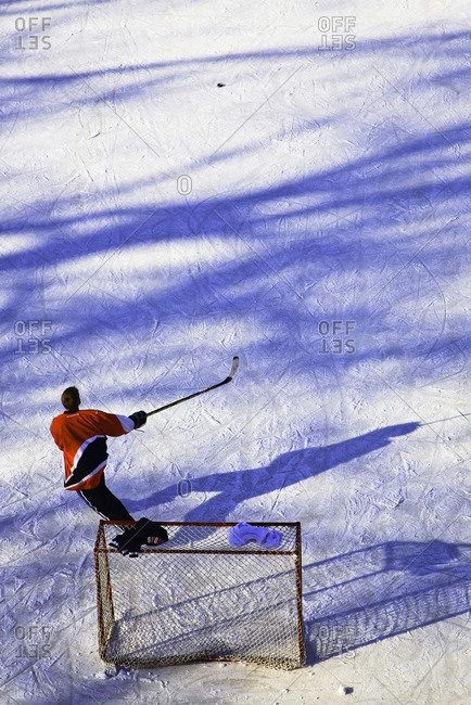 Teenage boy playing ice hockey on the frozen Assiniboine River.  The Forks, Winnipeg, Manitoba, Canada.
