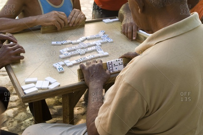 A group of elderly gentlemen playing a mean game of dominoes in the streets of Trinidad Cuba