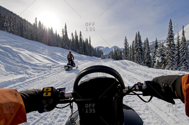 A pair of snowmobilers take to the trails in the Monashee mountains, just South of Valemount, in the North Thompson area, British Columbia, Canada.