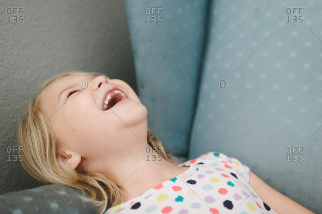 Girl lying on couch and laughing