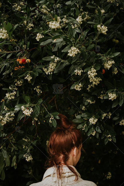 Woman with red hair by fruit tree