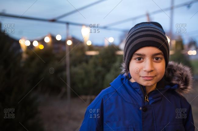 Boy in a toboggan and jacket at a Christmas tree lot