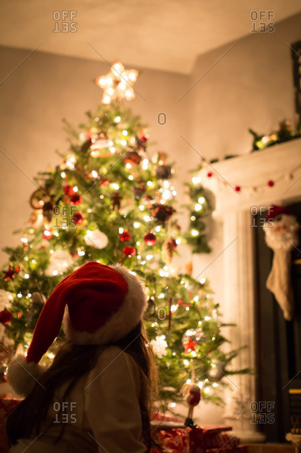 Little girl in a Santa hat looking at a lighted Christmas tree