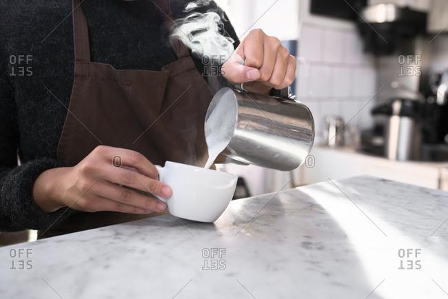 A barista putting milk into coffee