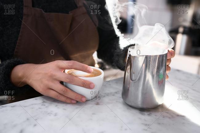 Barista adding steamed milk to coffee