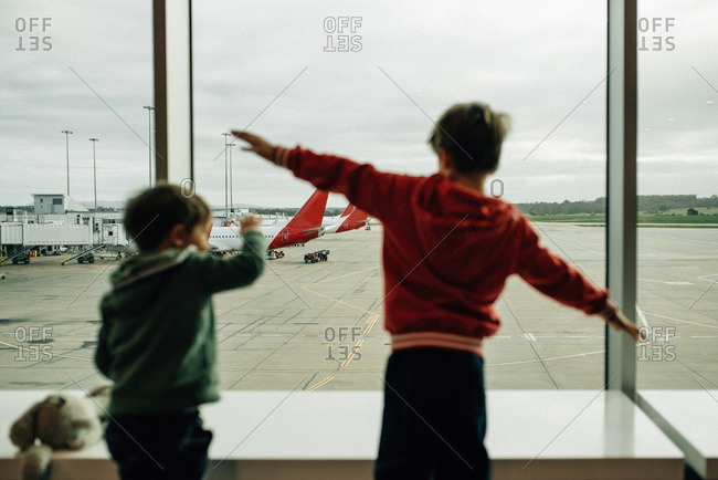 Boys looking out window at an airport while spreading arms
