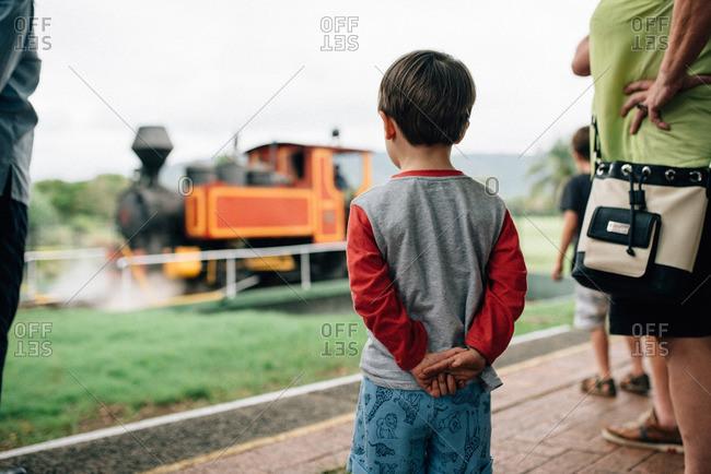 Little boy watching train pass by