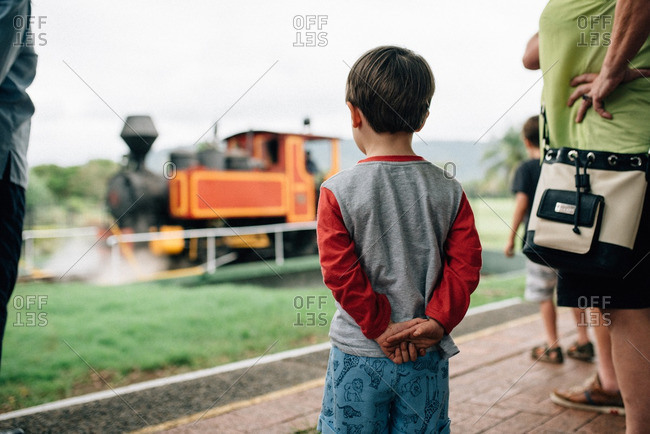 Little boy watching train pass by
