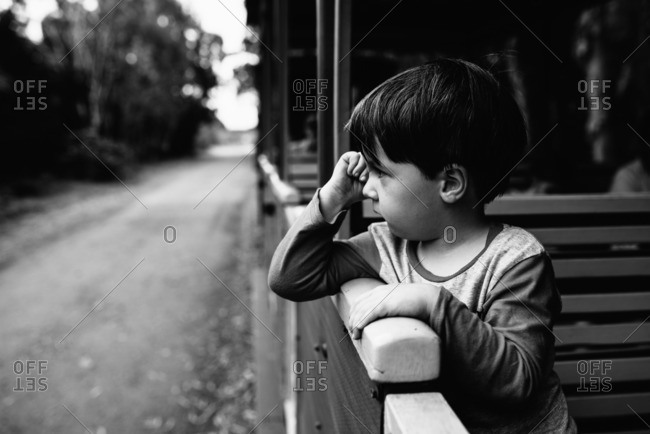 Little boy rubbing eyes while riding a train