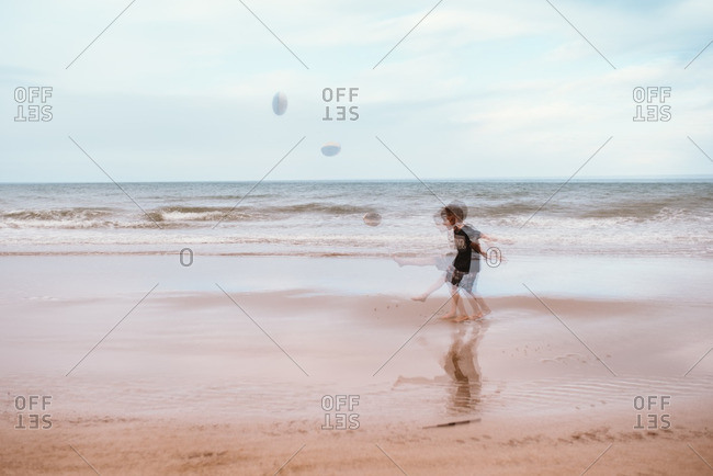 Blurred view of boy kicking football on a beach
