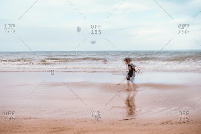 Blurred view of boy kicking football on a beach