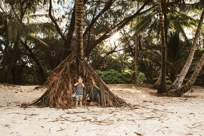 Father and son hiding under palm tree leaves on a beach