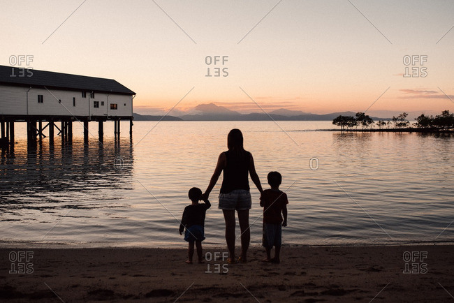 Silhouette of woman standing on beach holding son's hands