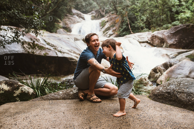 Father and son playing by a river in the forest